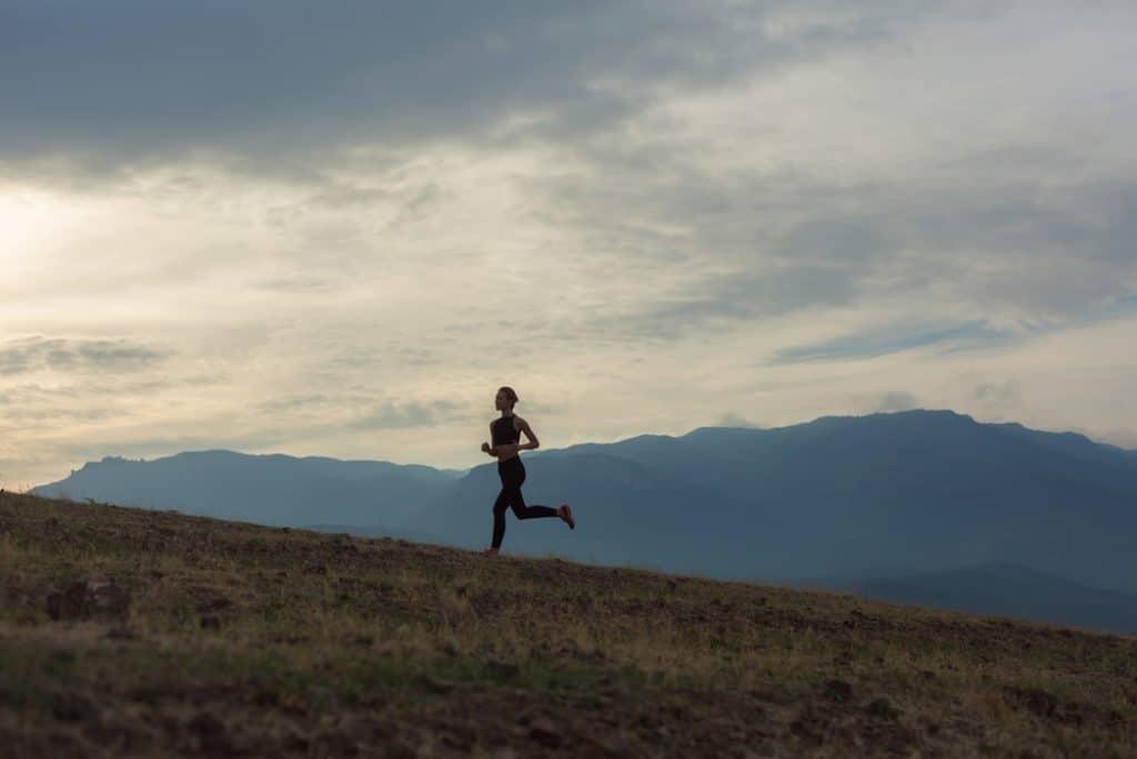 Silhouette of women running uphill