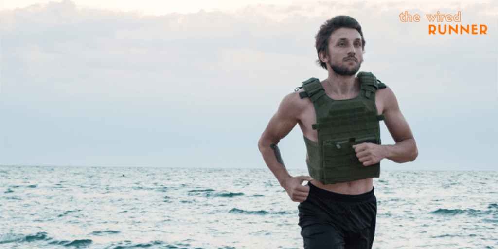Man running on beach with weight vest