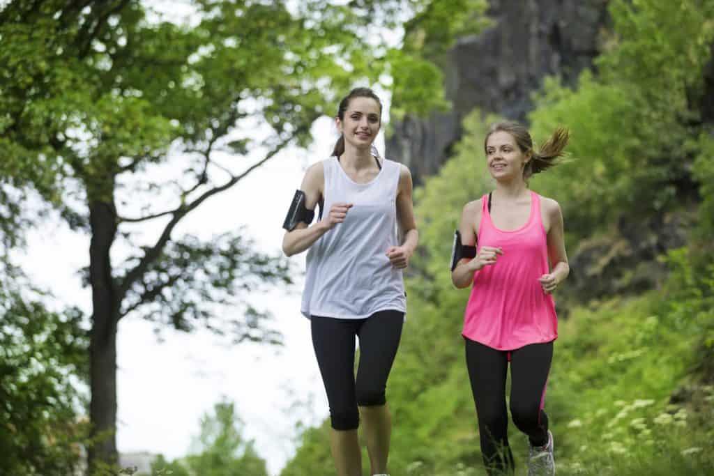 Dos mujeres atléticas corriendo al aire libre.  Acción y concepto de estilo de vida saludable.