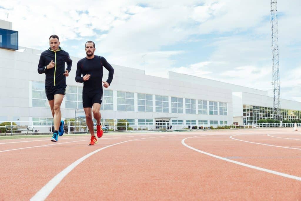 Grupo de gente joven de atletismo corriendo en el campo de la pista