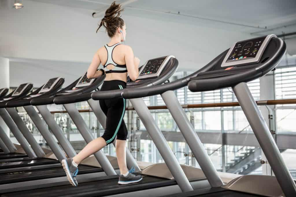 Fit brunette running on treadmill at the gym