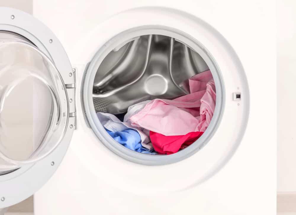 Modern washing machine with laundry, closeup