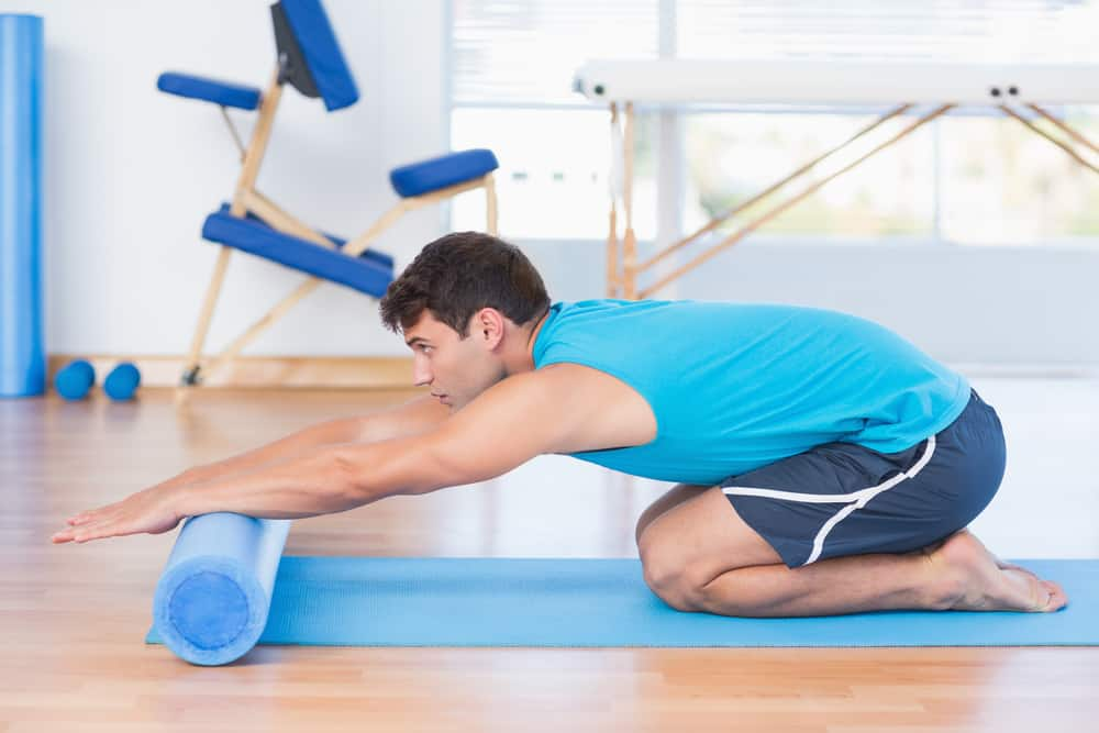 Man exercising with foam roller in fitness studio