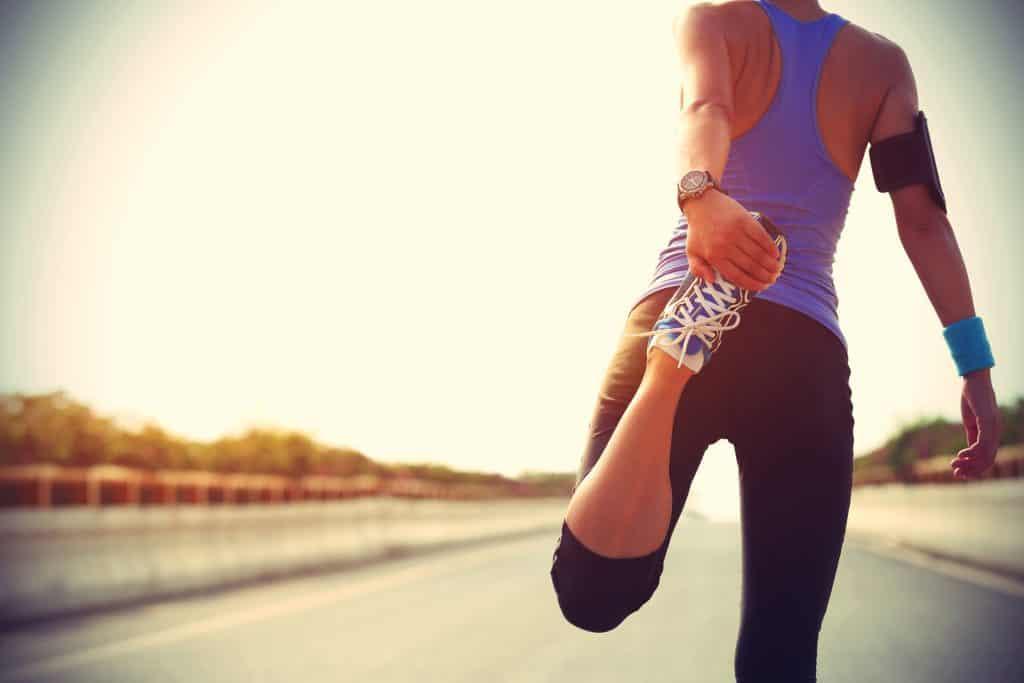 Corredor de mujer joven ftiness estirando las piernas antes de ejecutar