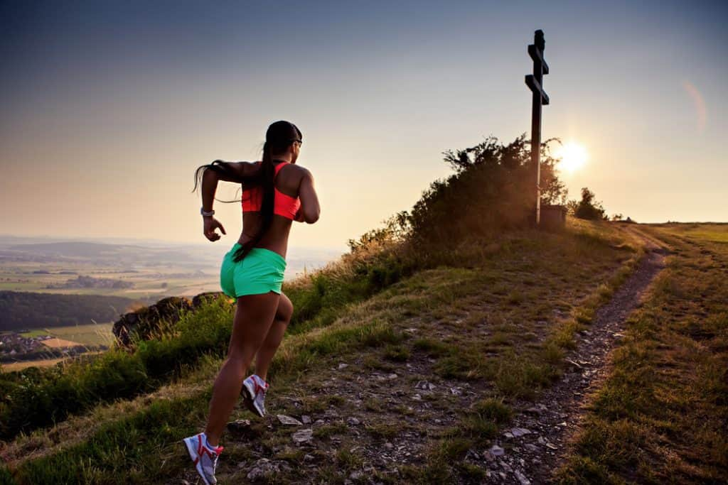 mujer joven corriendo en las montañas