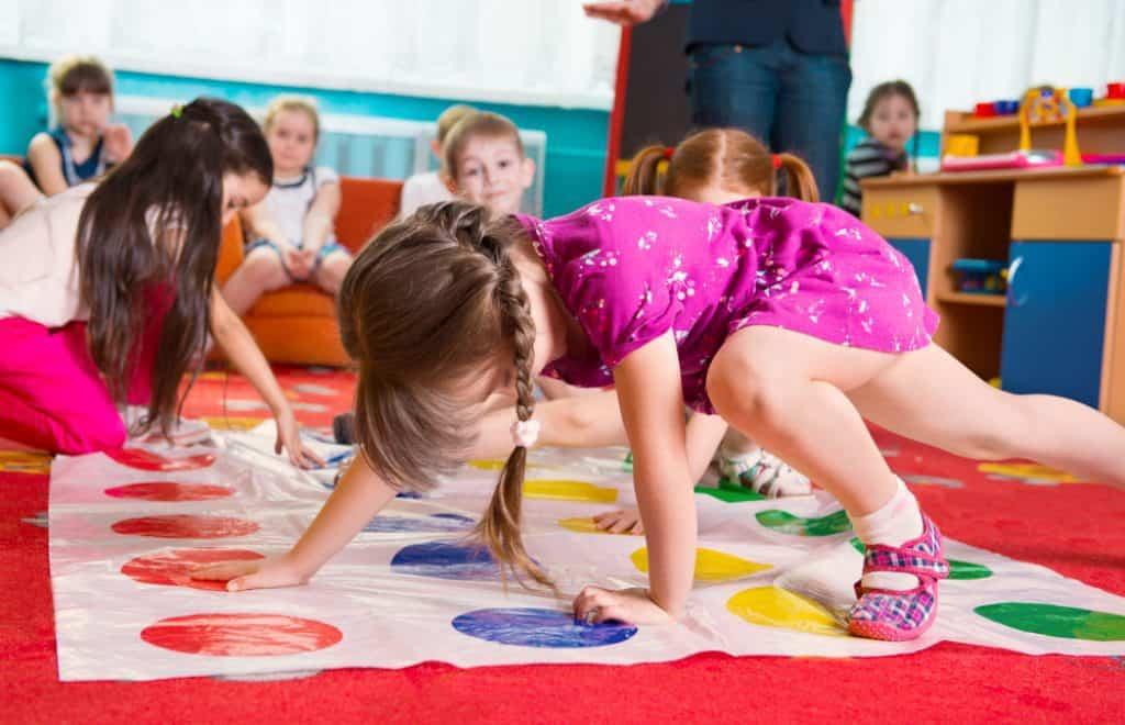 Lindos niños pequeños jugando en el juego twister